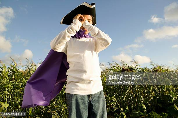 boy (6-8) in cape and hat with imaginary spyglass - tricornered hat stock photos and pictures