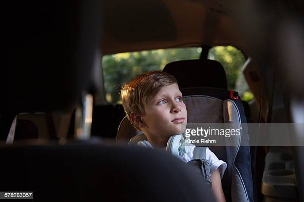 Boy in car back seat gazing out through window