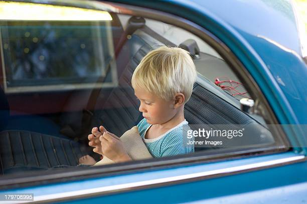 Boy in car back seat