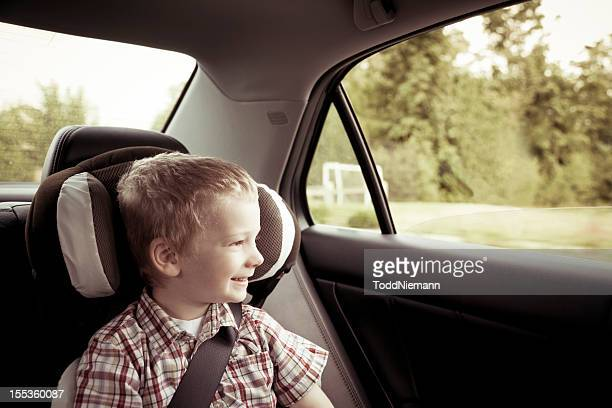 Boy in car seat riding in car with a big smile