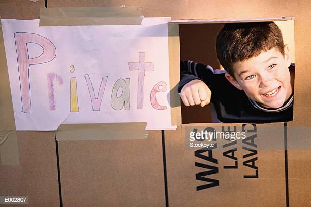 Boy in cardboard house, peeking head out of window