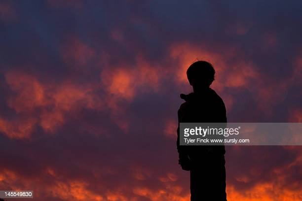 boy in cloudy sunset - sursly stock pictures, royalty-free photos & images