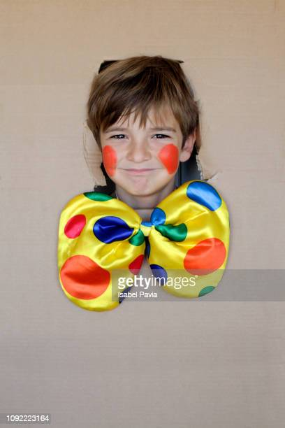 boy in clown costume, looking through a hole on cardboard - happy clown faces stock photos and pictures