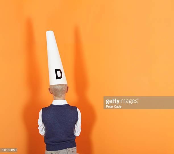 boy in corner wearing dunces hat