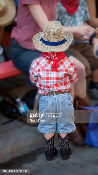 boy in cowboy costume standing at calgary stampede parade, rear view - calgary stampede stock pictures, royalty-free photos & images