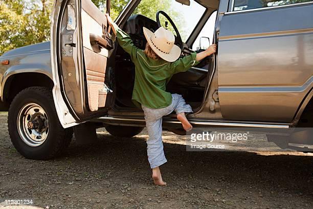 Boy in cowboy hat, climbing into station wagon