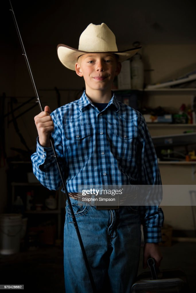 a23d42a1b72 Boy in cowboy hat with fishing rod on ranch Montana in winter   Stock Photo