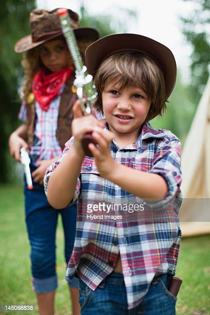 Boy in cowboy hat with toy pistol