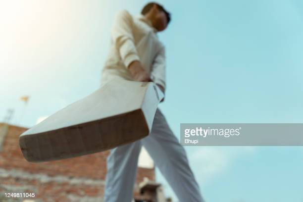 a boy in cricket uniform and doing batting practice. - cricket bat stock pictures, royalty-free photos & images