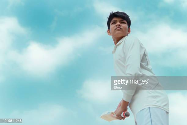 a boy in cricket uniform and doing batting practice. - batsman stock pictures, royalty-free photos & images