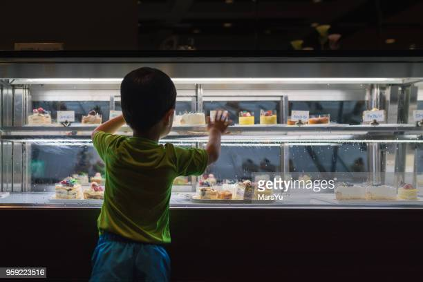 boy in culinary shop - chocolate shop stock pictures, royalty-free photos & images