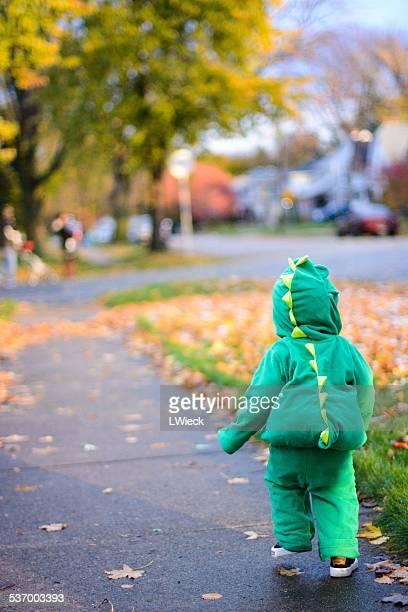 Boy in dinosaur costume walking on sidewalk