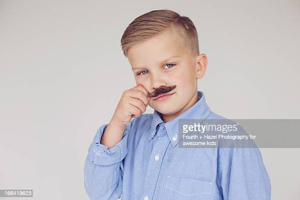 boy in dress shirt with fake moustache