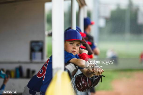 boy in dugout during little league baseball game - ncaa stock pictures, royalty-free photos & images