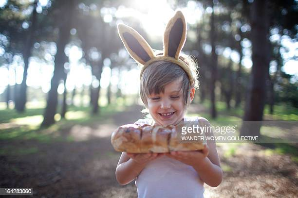 Boy in Easter bunny ears with hot cross buns