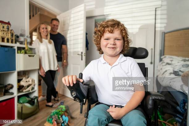 Boy in electric wheelchair smiling with proud parents in doorway
