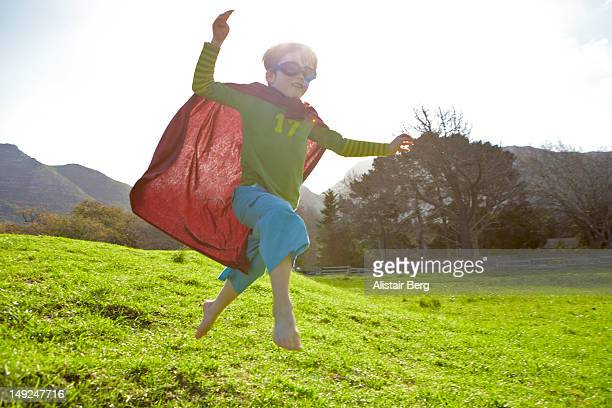 Boy in fancy dress jumping down a hil