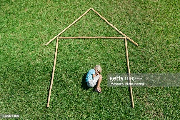 Boy in fetal position within outline of house, high angle view
