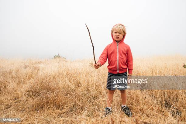 Boy in field holding stick, Fairfax, California, USA, North America