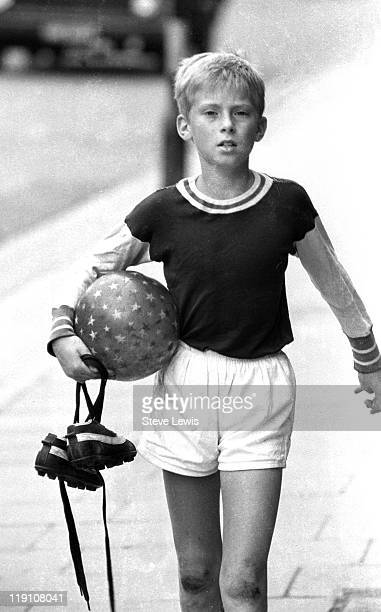 A boy in football gear carrying his boots and a ball east London circa 1970