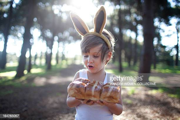 Boy in forest  bunny ears with hot cross buns