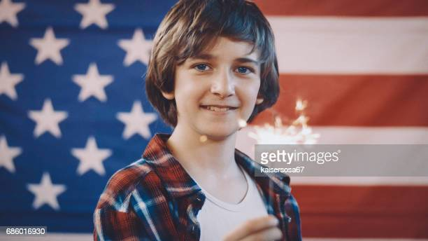 boy in front of american flag holding sparkler in hand