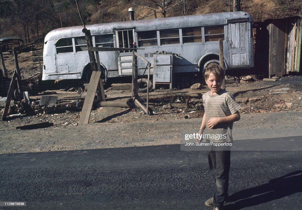 boy-in-front-of-an-old-bus-which-was-converted-into-a-house-pike-us-picture-id1129875638