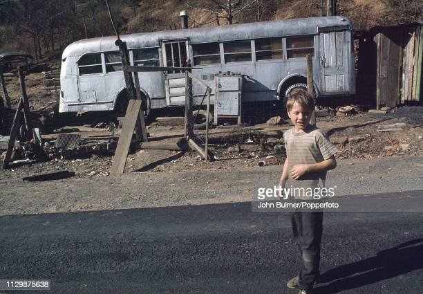 A boy in front of an old bus which was converted into a house Pike County Kentucky US 1967