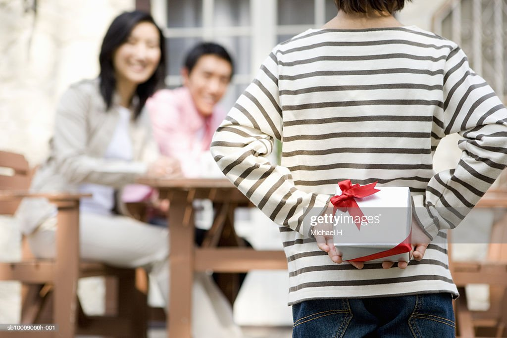 Boy (6-7) in front of family members, hiding gift box behind back : Stockfoto