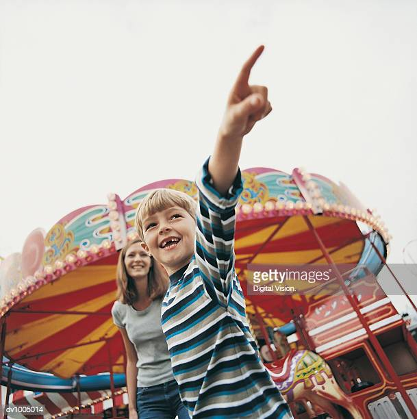 Boy in Front of Mother Pointing in Fairground
