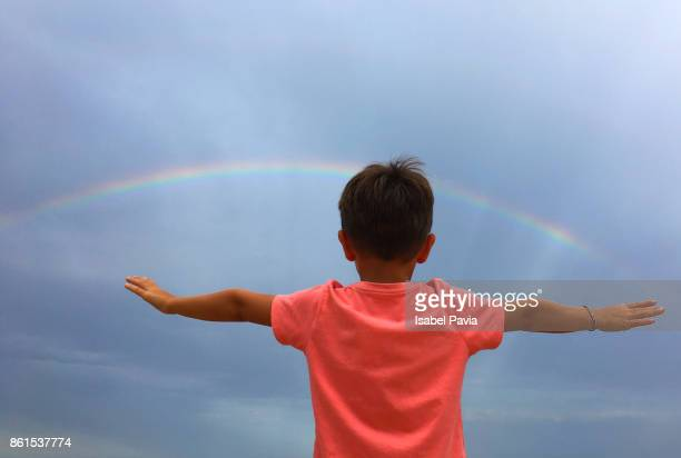 Boy (5-6) in front of rainbow