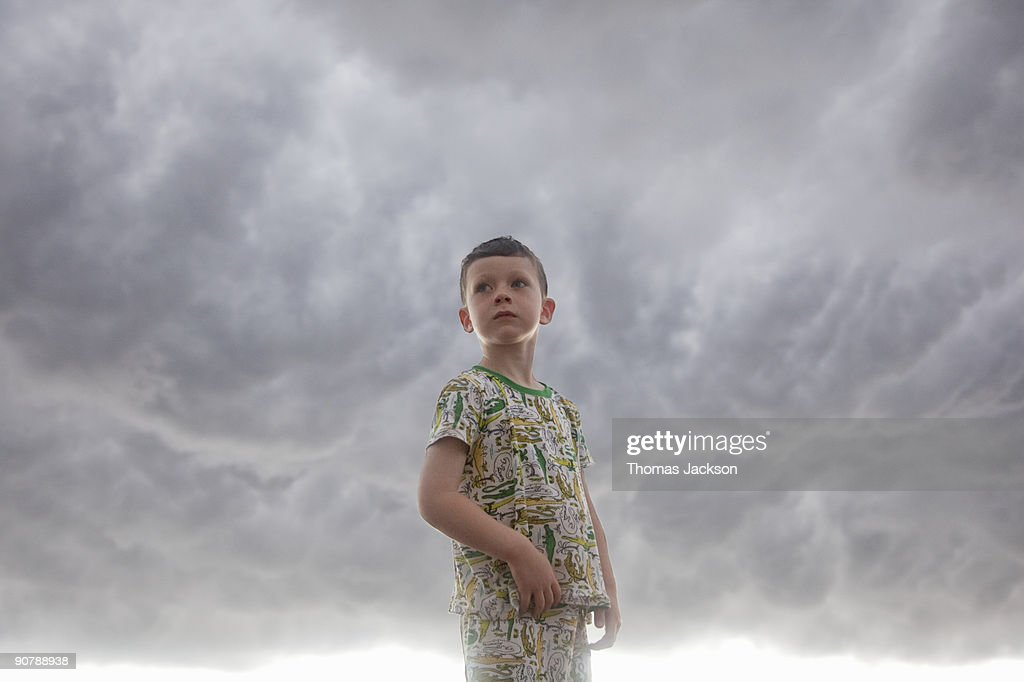 Boy in front of stormy skies : Bildbanksbilder