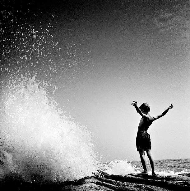 Boy In Front Of Wave. Wall Art
