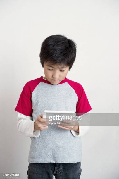 boy in game - handheld video game stock pictures, royalty-free photos & images