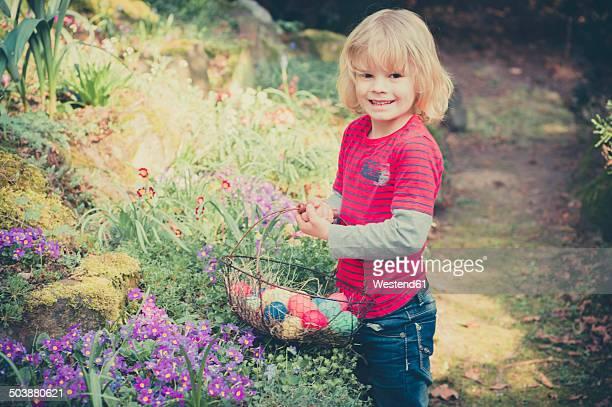 Boy in garden carrying Easter basket