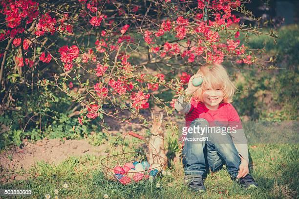 Boy in garden holding Easter egg