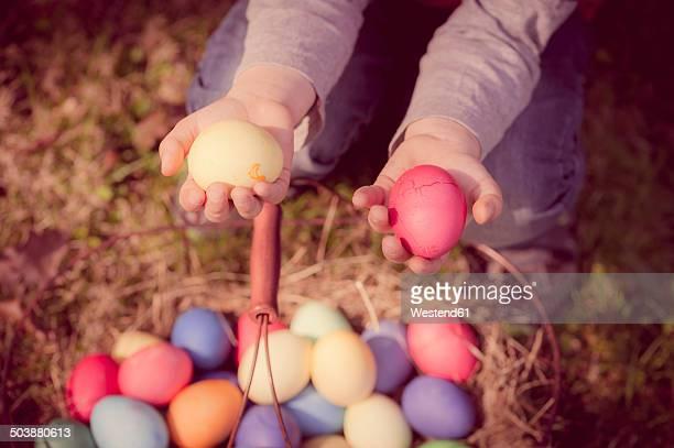 Boy in garden holding Easter eggs