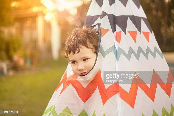 Boy in garden peeking out of teepee