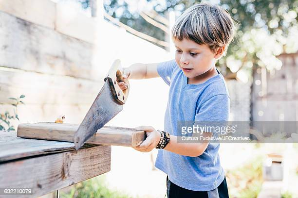 Boy in garden using saw, sawing plank of wood