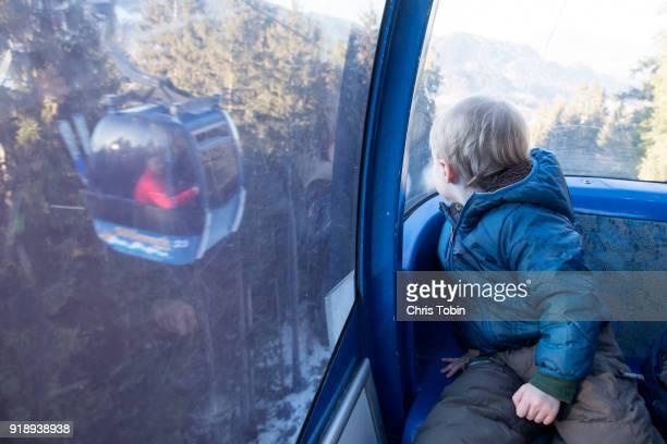 boy in gondola looking across to another gondola - gondel stock-fotos und bilder