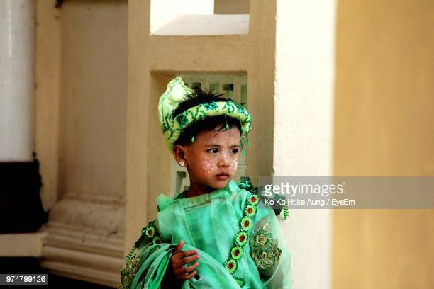 boy in green costume looking away white standing against wall - ko ko htike aung stock pictures, royalty-free photos & images