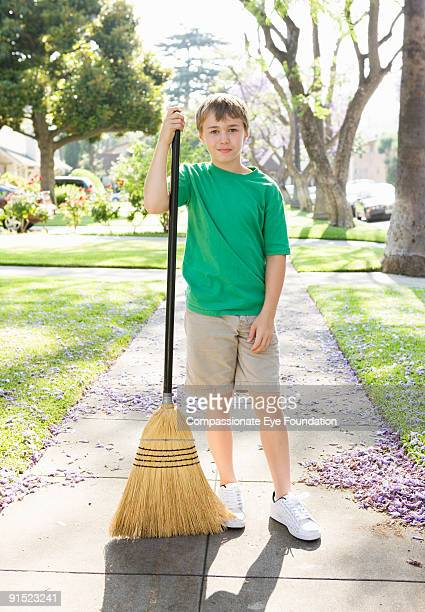 """boy in green tshirt holding broom on sidewalk - """"compassionate eye"""" stock pictures, royalty-free photos & images"""