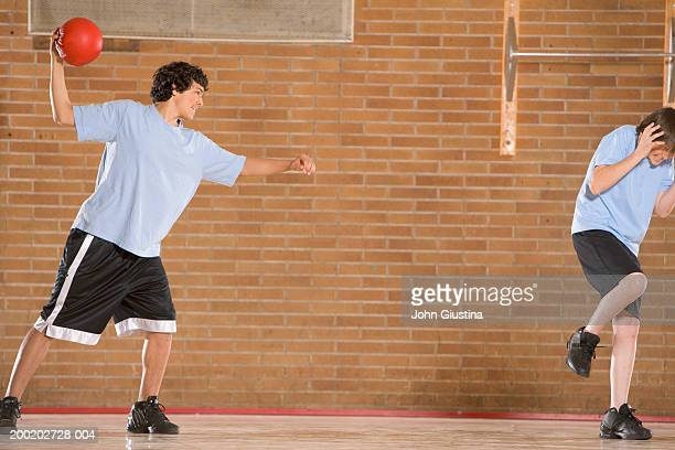 Boy (13-15) in gym throwing dodgeball at other boy