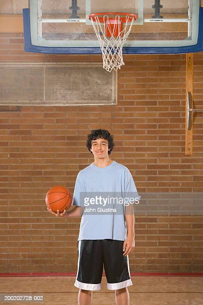 boy (13-15) in gym with basketball, portrait - 14歳から15歳 ストックフォトと画像