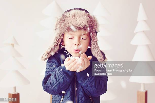 boy in hat blowing snow