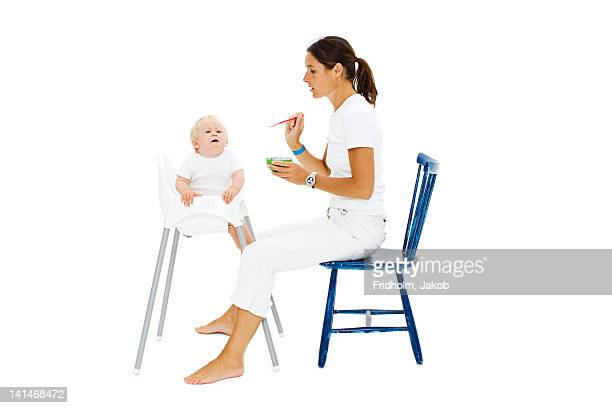 Boy in high chair being fed by mother