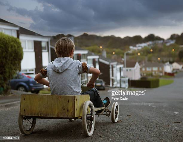Boy in homemade go kart at top of street