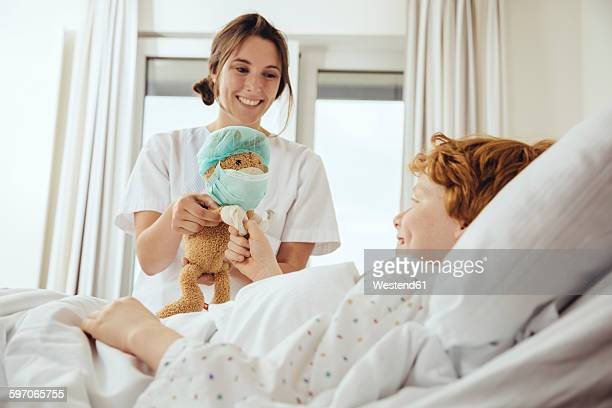 Boy in hospital bed receiving toy from nurse