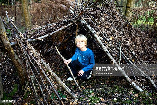 Boy in hut made of Tree branches