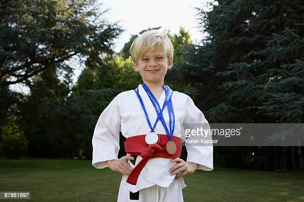 boy in karate kit,  with medals - medallist stock pictures, royalty-free photos & images